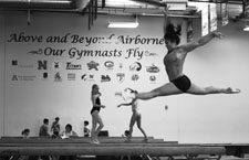 Chuang performs her balance beam routine in view of Airborne's motto and collage of the gym's alum's colleges.
