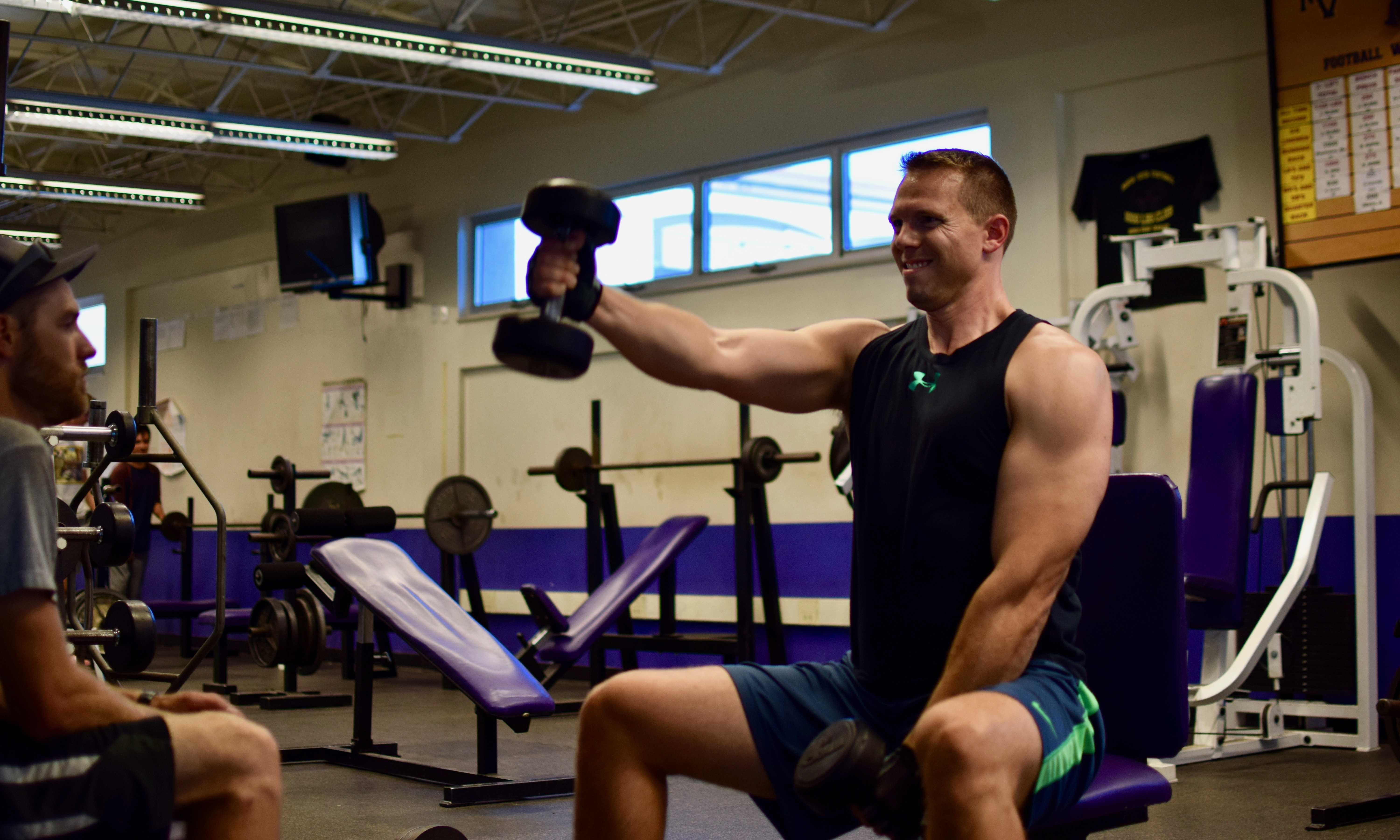 Guidance counselor Clay Stivers performs forward raises in the MVHS weight room. Stiver opens up the room from 4 to 6pm on Mondays and Wednesdays. Photo by Om Khandekar.