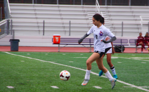Senior Rebecca Noordeen dribbles up the field preceding the goal by freshman Skylar Ploshay. The team did well to find open players and move the ball up fast up the field. Photo by Jasmine Lee.