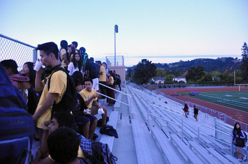 Seniors stand by the bleachers drinking hot chocolate and eating bagels as the sun rises. Senior Sunrise relocated to the bleachers before the sunrise occurred at 6:28 a.m.