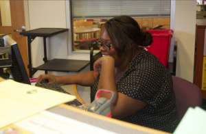 Monique Balentine sits at the desk where she coordinates the Study Buddies Society program. She organizes student tutors so that struggling students can be helped. Photograph by Tanisha Dasmunshi