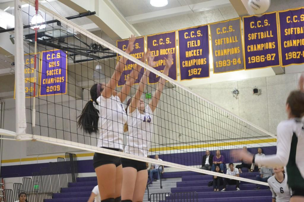 Freshman Kelly Bishop and junior Hannah Pollek jump to block Homestead's spike on Oct. 3. Photo by Colin Kim