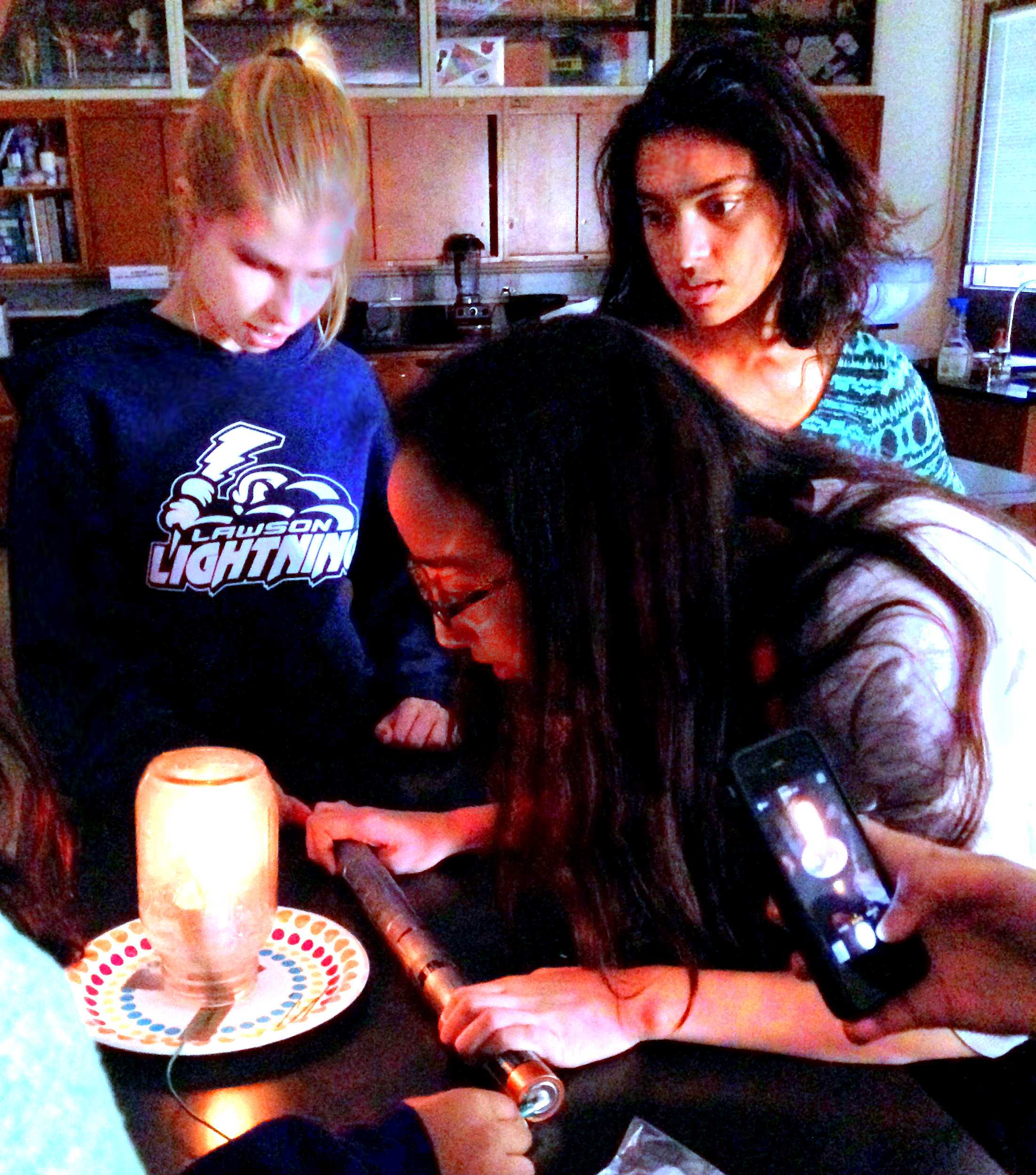WiSTEM Internal Vice President senior Emma Lewis helps demonstrate the light bulb experiment for freshmen Johanna Karras and Kalpana Gopalakrishnan. The experiment, conducted at the club's meeting on Nov. 13, involved creating a make-shift lightbulb using batteries, wires and pencil lead. Photo by Varsha Venkat.