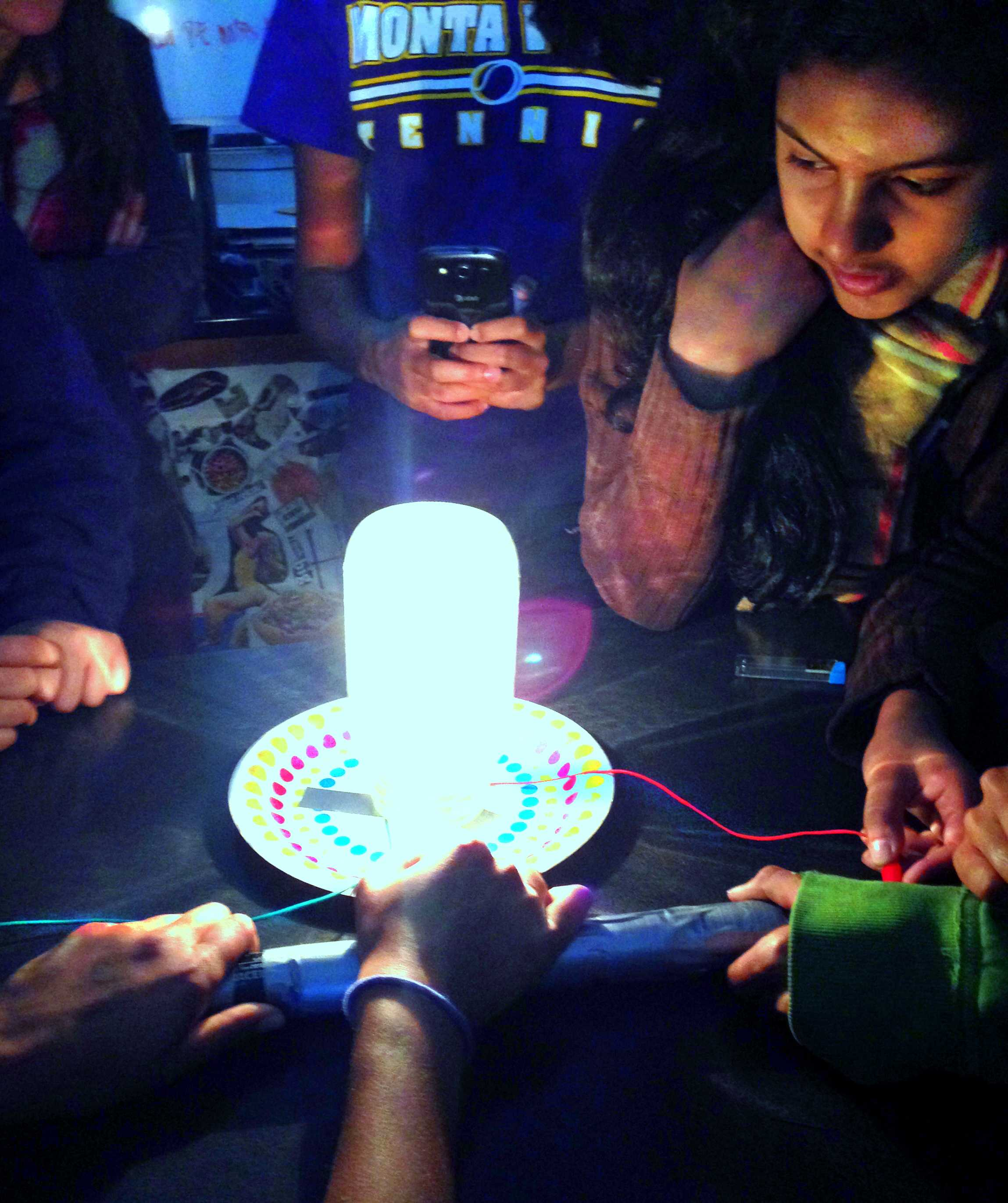 WiSTEM members watch the make-shift lightbulb that they created. The lab tested whether the quantity of lead used affects the brightness of the light. Photo by Varsha Venkat.