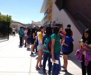 Freshmen wait in line for Running of the Bulls outside the cafeteria on Aug. 12. Some students were not aware of the location change, but overall, administration and volunteers preferred the cafeteria over the field house. Photo by Elia Chen.