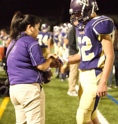 Athletic trainer Marie Gishifu bandages a deep cut Junior James Midgal got during MVHS' homecoming game again against PAHS. Photo by Trisha Kholiya.