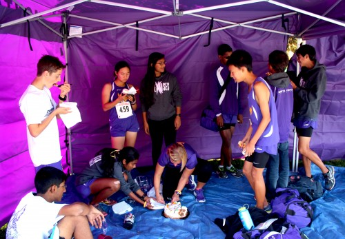 After all the varsity races, the team surprised sophomore Parvathi Meyyappan with a carrot cake to celebrate her birthday. Flatow and the runners often describe themselves as a big cross country family. Photo by Sharon Tung.