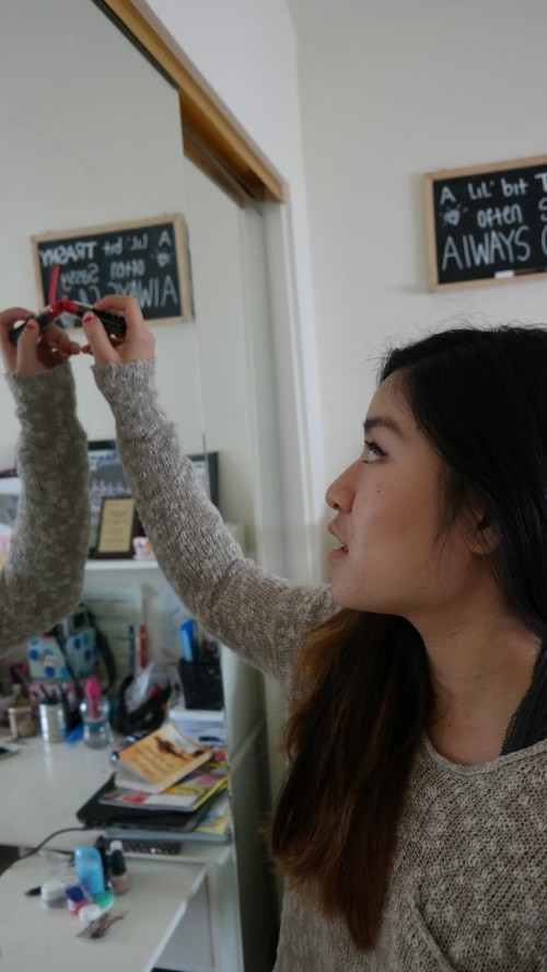 Junior Emily Leung writes a message on her bedroom mirror. Leung writes reminders on her mirror regularly using lipstick. Photo by Rhonda Mak