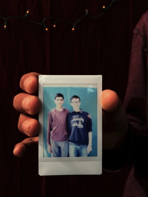 Senior Preetham Gujjula holds a polaroid of him and junior Willy Chao. The two received the picture for free after helping set up.