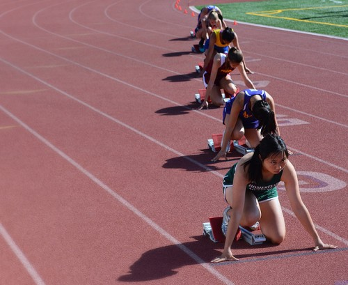 A Homestead HS athlete looks up before the start of the 100 m race. Most athletes completed a few practice starts before their event began.