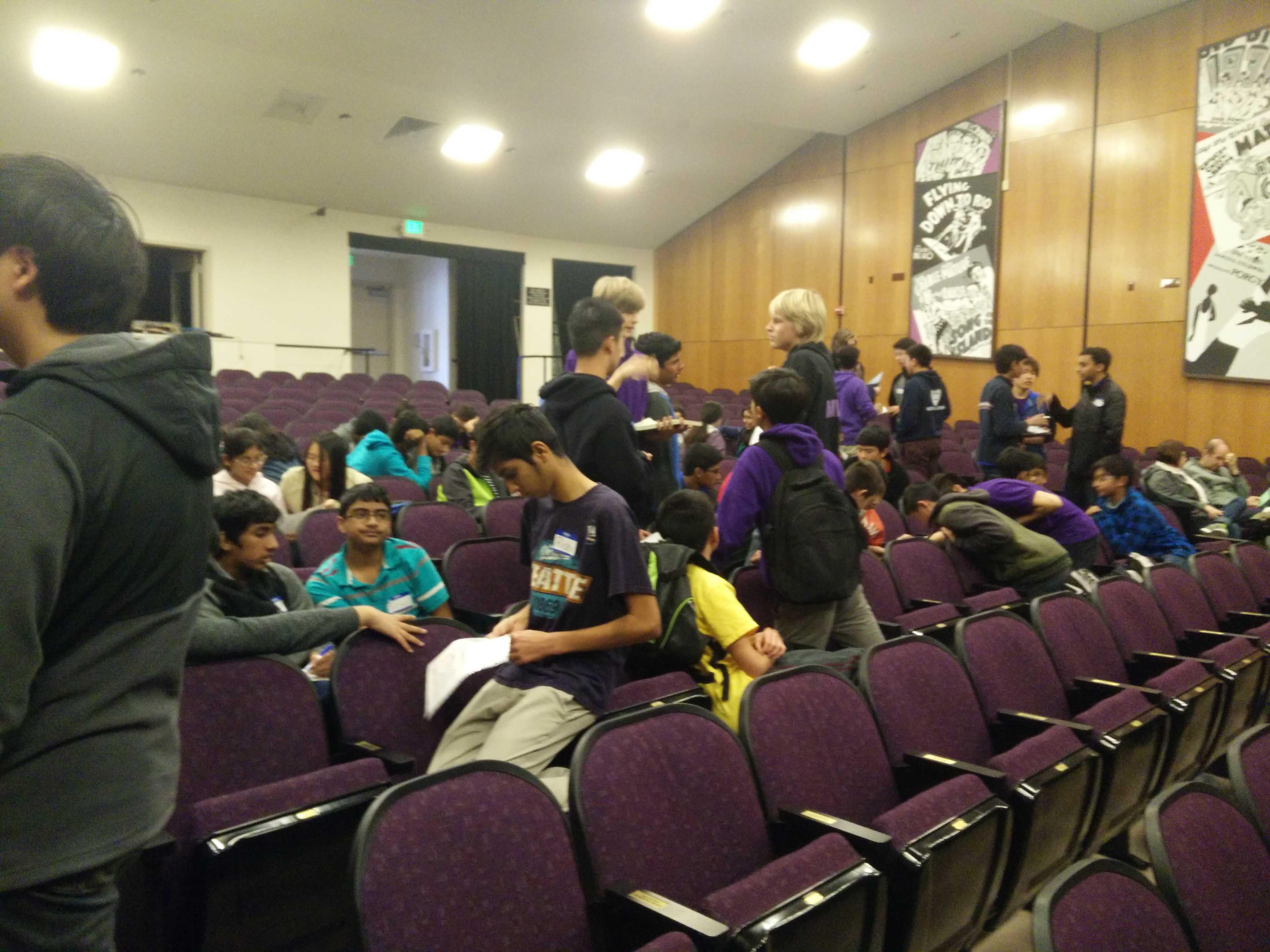 Robotics team members exchange strategies in small groups in the auditorium.