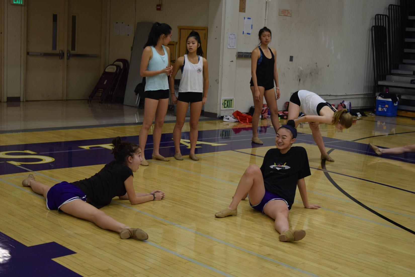 Sprawled out across the gym floor, dancers juniors Nicole Pound and Erin Lewis stretch as they chat with each other. Dancers waiting their turn frequently spent their time stretching to keep their muscles warm.