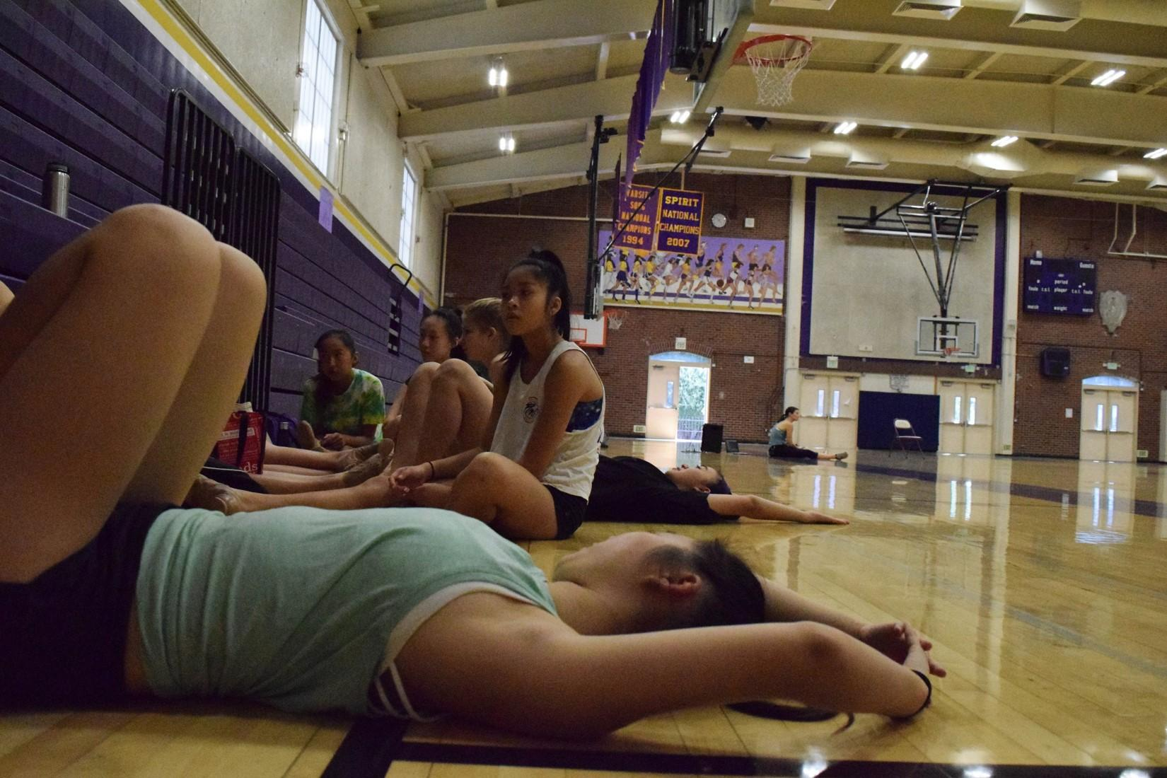 Senior and dance team captain Cherie Kim lies down on the ground and stretches out in between rehearsing. As Lund worked with different parts of the routine at a time, the Marquesas could take a break to snack, chat and watch the routine come together.