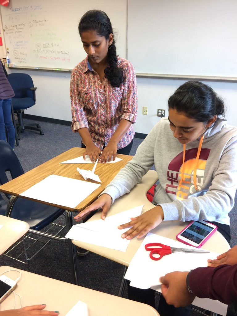 Junior and ArtReach treasurer Shivika Sivakumar makes origami cranes with a club member. ArtReach members made origami cranes during their first meeting. Photo by Dylan Tsai.