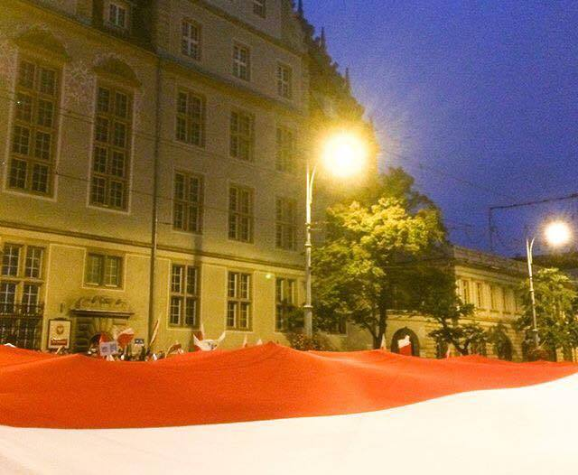 Protesters in Gdańsk unfurl a Polish flag outside of a courthouse. Photo used with permission from Jeremi Kalkowski.
