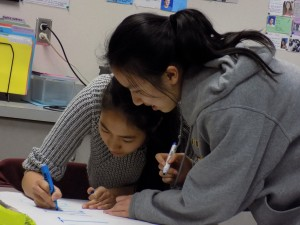 ArtReach club members making posters to promote their competition. The posters will be placed around school on Feb. 14.Photo by Sarah Young.